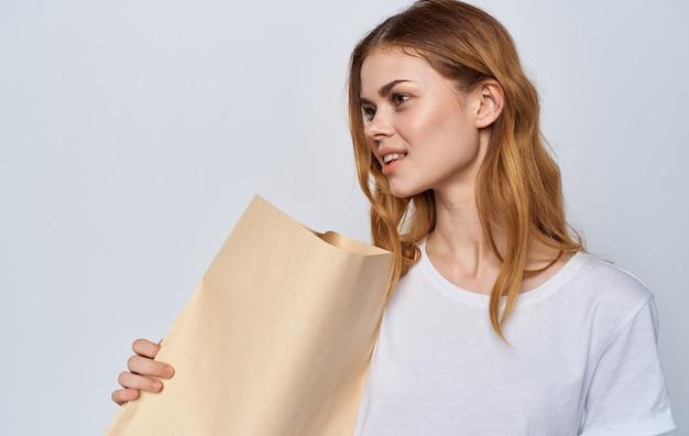 Wesoła kobieta w białej koszulce z pakietem w dłoniach zakupy