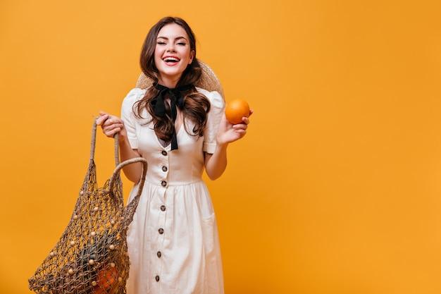 Wesoła kobieta w białej sukni z torbą na zakupy i pomarańczy na na białym tle.