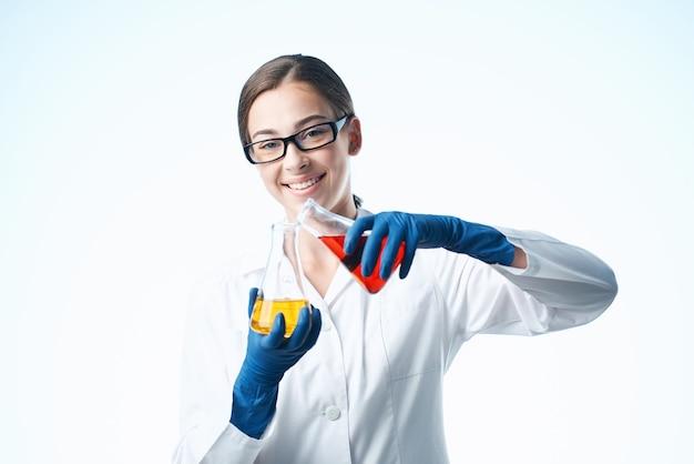 Wesoła kobieta w białym fartuchu analizuje eksperymenty chemiczne