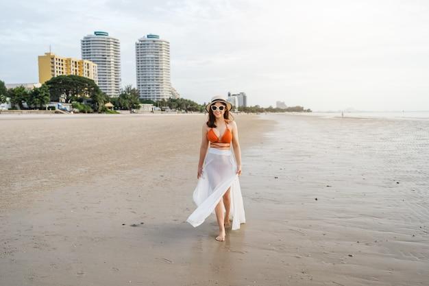 Wesoła kobieta w bikini spaceru na plaży