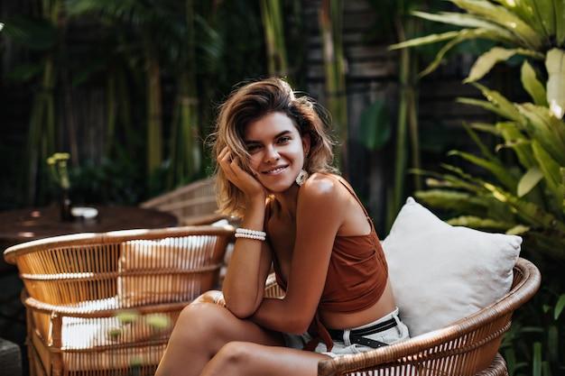 Wesoła kobieta w brązowych spodenkach i dżinsowych szortach uśmiecha się w ulicznej kawiarni