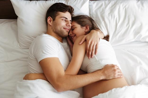 Wesoła kobieta w ciąży leży w łóżku z mężem