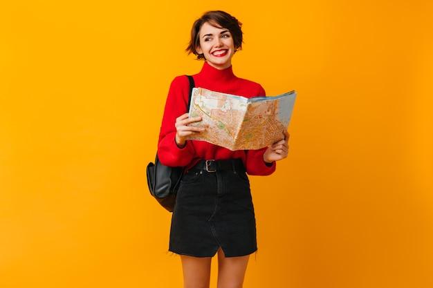 Wesoła kobieta w czarnej spódnicy przygotowuje się do podróży