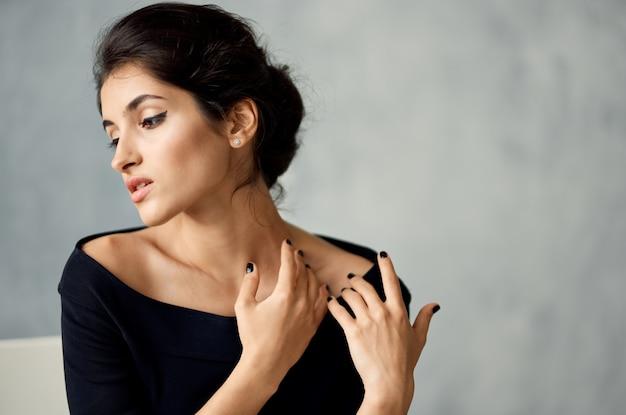 Wesoła kobieta w czarnej sukni glamour studio mody w eleganckim stylu