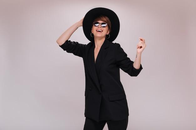 Wesoła kobieta w czarnym garniturze i kapeluszu taniec na białym tle. krótkowłosa dama w ciemnej kurtce i spodniach porusza się i uśmiecha na odosobnionym