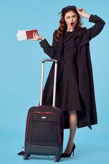 Wesoła kobieta w czarnym płaszczu podróż służbowa podróż pasażera na niebieskim tle