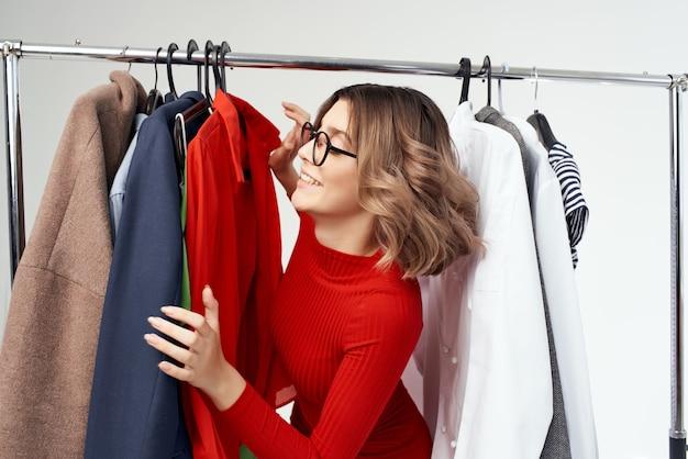 Wesoła kobieta w czerwonej kurtce w pobliżu detalicznych emocji szafa. zdjęcie wysokiej jakości