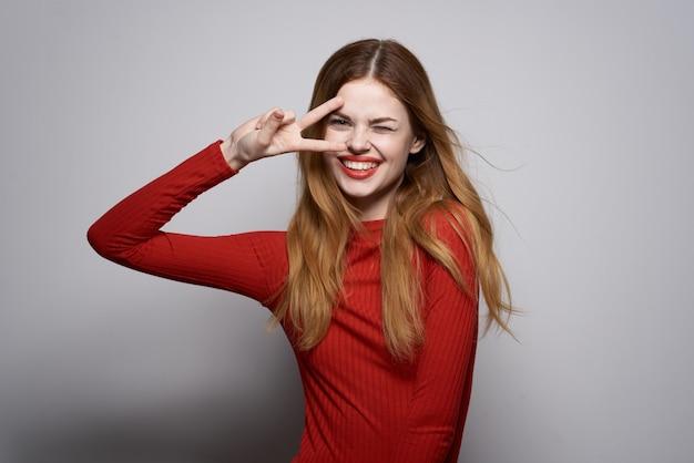 Wesoła kobieta w czerwonej sukience pozuje luksusową dłoń gest studio