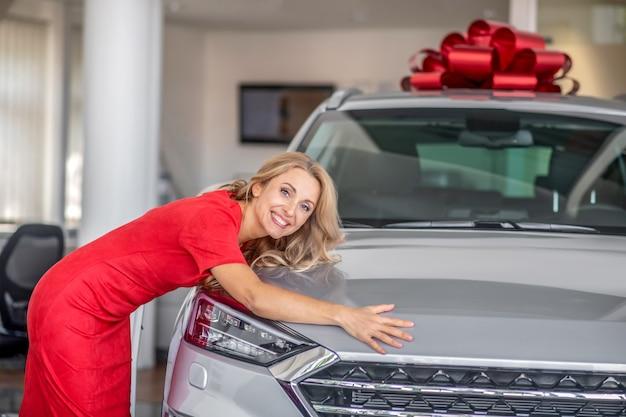 Wesoła kobieta w czerwonej sukience przytula nowy samochód