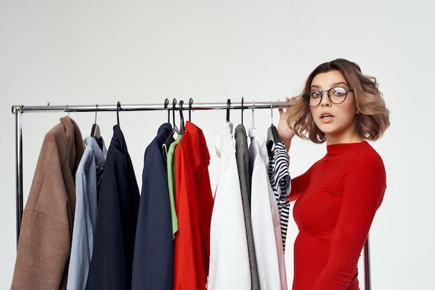 Wesoła kobieta w czerwonej sukience zakupoholiczka wybierająca ubrania na zakupy w sklepie jasnym tle