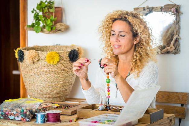 Wesoła kobieta w domu robi bransoletki i naszyjniki z kolorowymi koralikami