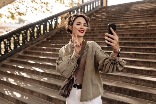 Wesoła kobieta w fajną kurtkę i lekkie dżinsy dokonywanie selfie. młoda kobieta z falowanymi włosami pokazuje znak pokoju na zewnątrz.
