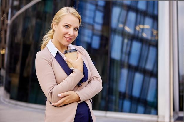 Wesoła kobieta w garniturze stoi w pobliżu centrum biznesowego z kawą na wynos