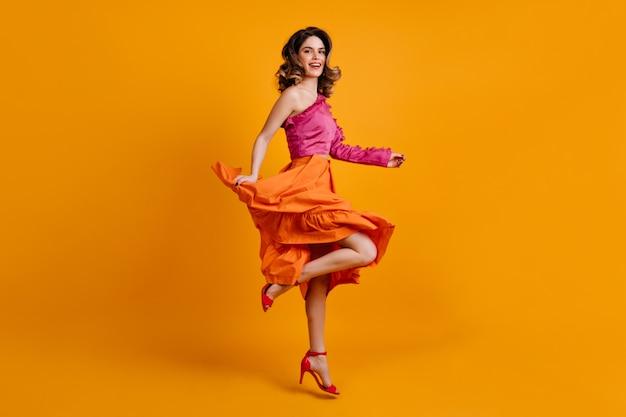 Wesoła kobieta w jasnej spódnicy taniec