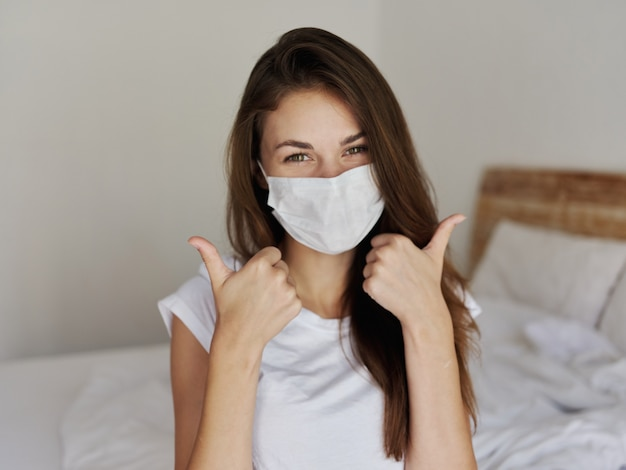 Wesoła kobieta w masce medycznej pokazując kciuk do góry