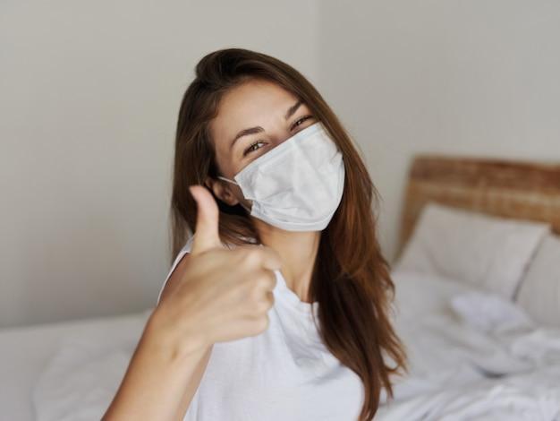 Wesoła kobieta w masce medycznej pokazuje kciuk w górę