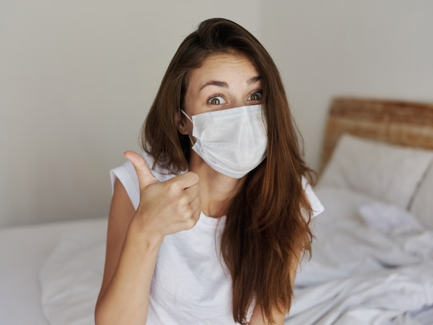 Wesoła kobieta w masce medycznej siedząca na łóżku kciuk w górę