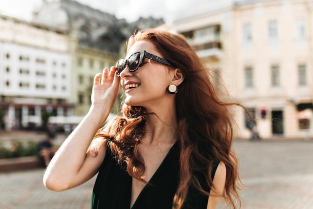 Wesoła kobieta w modnych okularach przeciwsłonecznych śmieje się na zewnątrz
