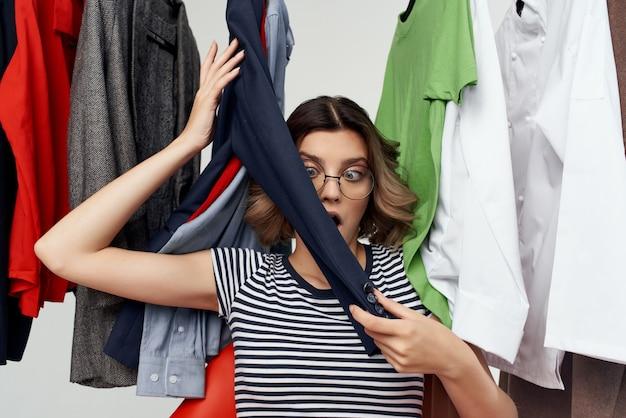 Wesoła kobieta w okularach obok ubrań moda zabawa detaliczna emocje