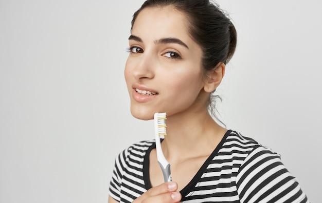 Wesoła kobieta w pasiastej koszulce higieny szczoteczki do zębów. wysokiej jakości zdjęcie