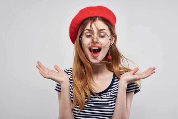 Wesoła kobieta w paski t-shirt czerwone usta gest rękami lato. zdjęcie wysokiej jakości