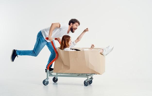 Wesoła kobieta w pudełku na wózku cargo i energiczny kurier w dżinsach i koszulce