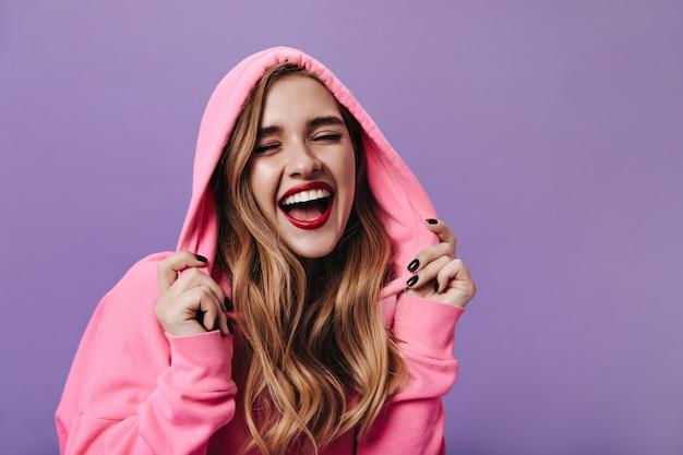 Wesoła kobieta w różowej bluzie z kapturem śmiejąca się na izolowanej ścianie