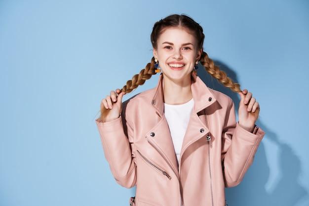 Wesoła kobieta w różowej kurtce warkocze ozdoba pozowanie w nowoczesnym stylu
