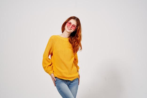 Wesoła kobieta w różowych okularach gestykuluje z jej rękami żółty sweter studio. wysokiej jakości zdjęcie