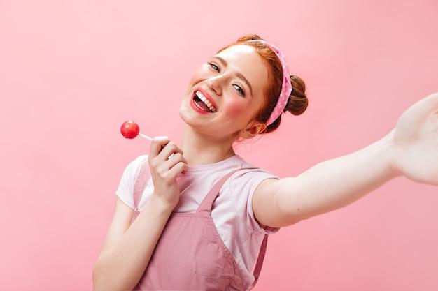 Wesoła kobieta w różowym kombinezonie i białej bluzce trzyma cukierki i robi selfie na różowym tle.