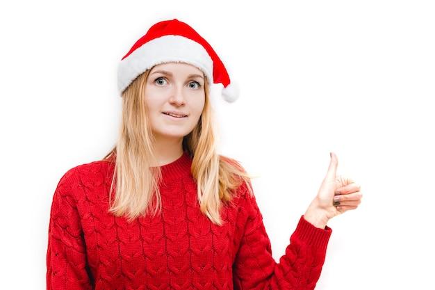 Wesoła kobieta w santa hat pokazuje kciuk. dziewczyna patrząc na kamery i uśmiechając się na białym tle.