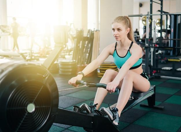 Wesoła kobieta w sportowej robi ćwiczenia na maszynie do symulacji wioślarstwa w siłowni.