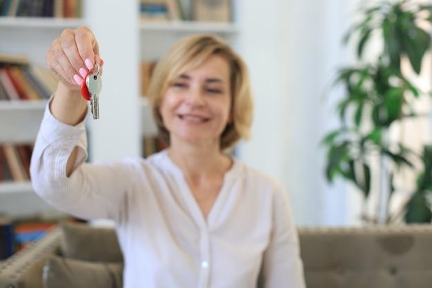 Wesoła kobieta w średnim wieku, agentka nieruchomości, siedząca na kanapie, trzymająca klucze do nowego domu.