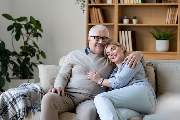 Wesoła kobieta w średnim wieku w casualwear pochylająca się do ramienia swojego starszego ojca, jednocześnie relaksując się na kanapie w domu