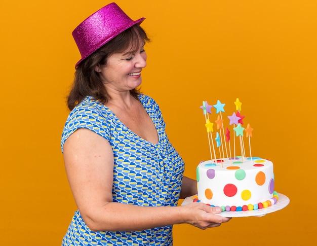 Wesoła kobieta w średnim wieku w imprezowym kapeluszu trzymająca tort urodzinowy patrząca na niego z uśmiechem na twarzy