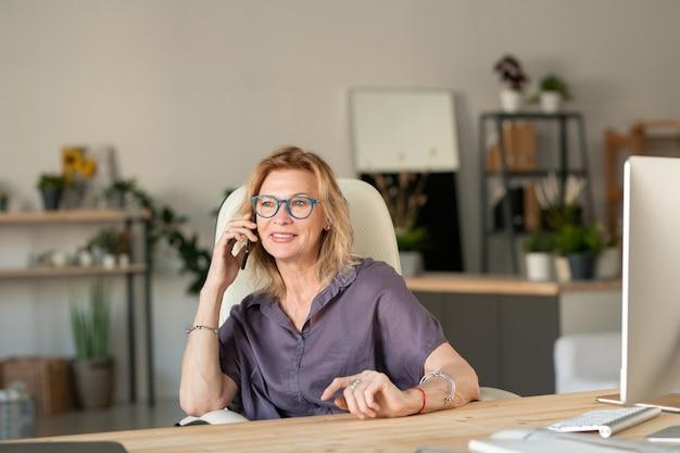 Wesoła kobieta w średnim wieku ze smartfonem przez ucho dzwoniąc przez miejsce pracy przed monitorem komputera, pozostając w domu