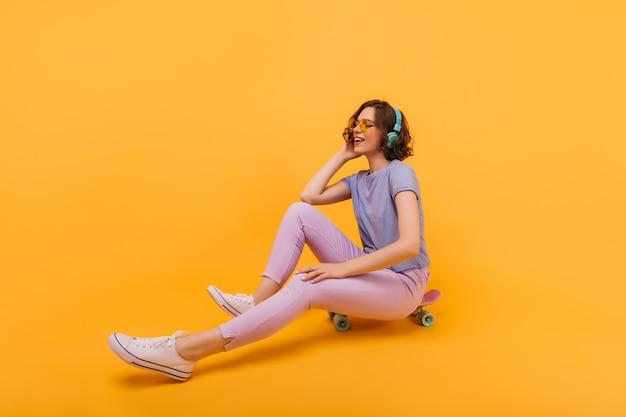 Wesoła kobieta w stylowy strój siedzi na deskorolce z zamkniętymi oczami. cudowna dziewczyna pozuje na longboardzie w żółtych okularach.