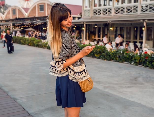 Wesoła kobieta w stylowym stroju rozmawia przez telefon komórkowy i uśmiecha się na riverfront w bangkoku