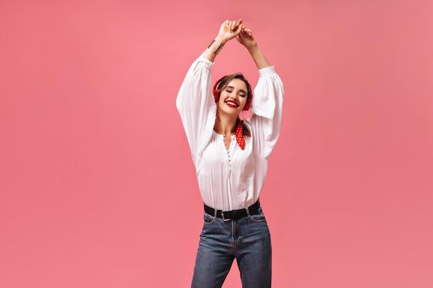 Wesoła kobieta w stylowym stroju z radością słucha muzyki w słuchawkach. jasna dama w koszuli i dżinsach z czarnym paskiem uśmiecha się na różowym tle.