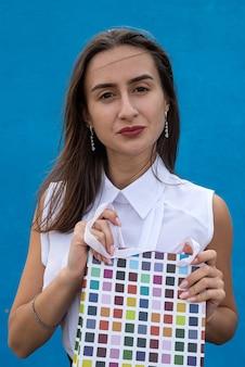 Wesoła kobieta w stylu biznesu tkaniny trzymać torby po wyprzedaży okazje na niebieski kolor tła. zakupy w stylu życia lub zakupy online