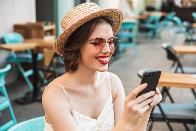 Wesoła kobieta w sukience i słomkowym kapeluszu za pomocą smartfona