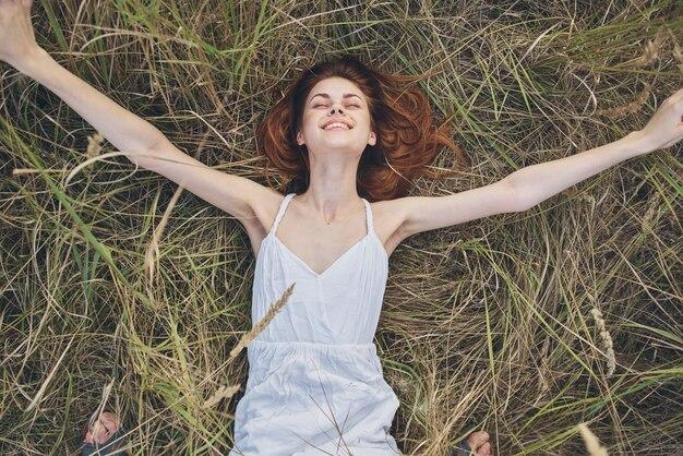 Wesoła kobieta w sukience leży na trawie odpoczynku natury