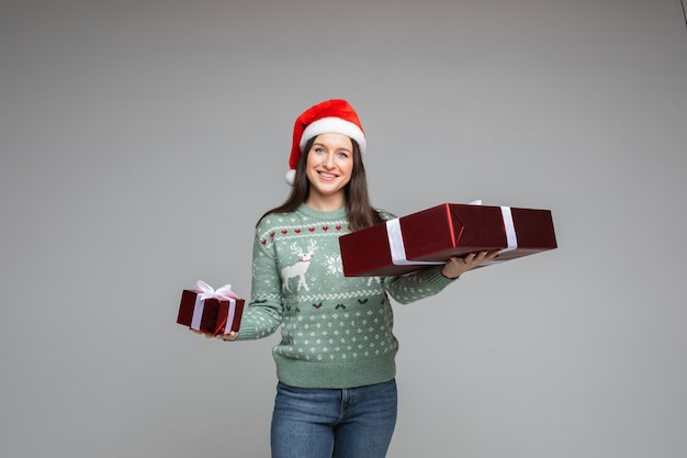Wesoła kobieta w swetrze i bożonarodzeniowym kapeluszu trzyma dwa pudełka ze świątecznymi prezentami