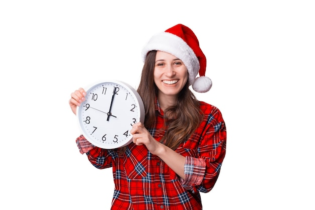 Wesoła kobieta w świątecznym kapeluszu trzyma zegar ścienny.