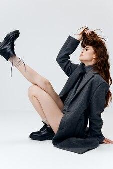 Wesoła kobieta w szarym płaszczu i butach na jasnym tle