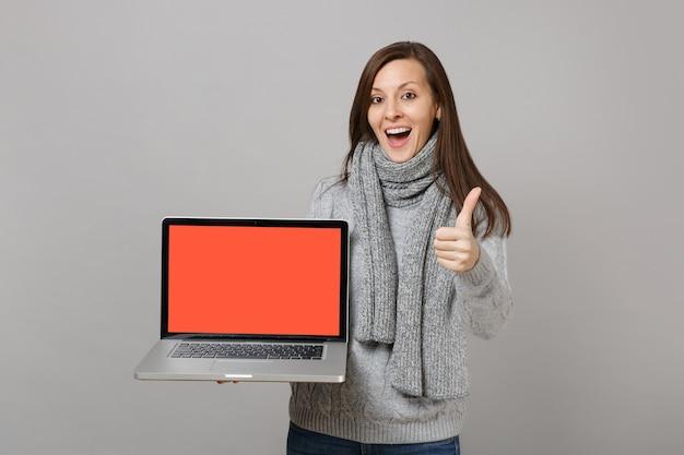 Wesoła kobieta w szarym swetrze, szalik pokazując kciuk do góry, przytrzymaj komputer przenośny pc z pustym pustym ekranem na białym tle na szarym tle. zdrowy styl życia online leczenie konsultacji koncepcji zimnej pory roku.