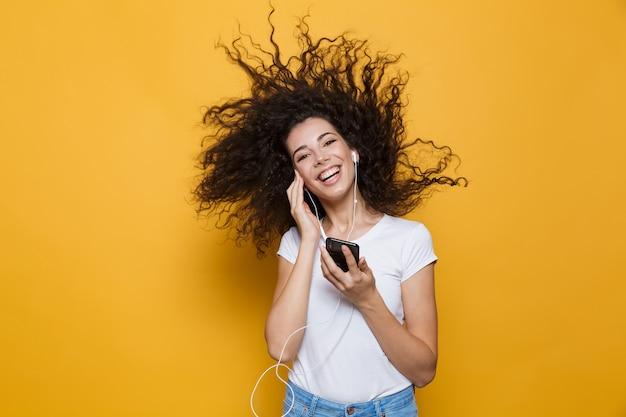 Wesoła kobieta w wieku 20 lat z kręconymi, trzęsącymi się włosami, trzymająca smartfona i słuchająca muzyki przez słuchawki izolowane na żółto