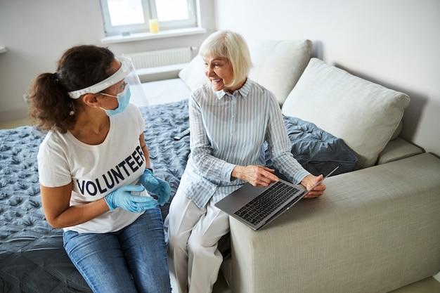 Wesoła kobieta w wieku z laptopem na łóżku i słuchanie wyjaśnień pracownika opieki na temat rzeczy na wyświetlaczu