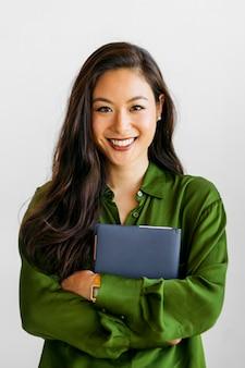 Wesoła kobieta w zielonej koszuli trzymająca niebieski notatnik