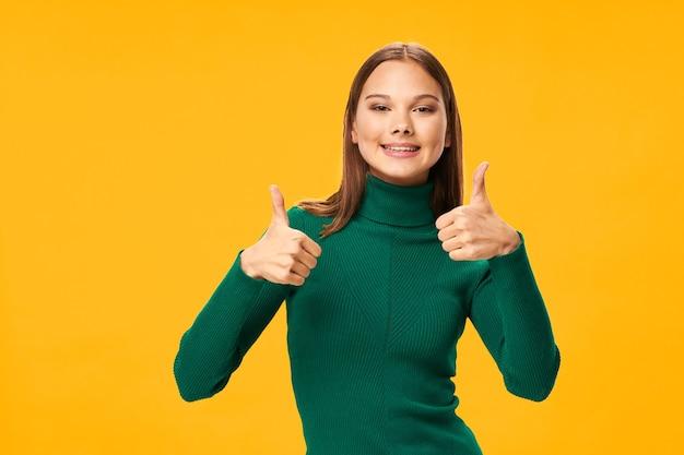Wesoła kobieta w zielonym swetrze gestykuluje rękami na żółtym tle
